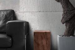 Tabla de madera del sofá negro con la escultura de la raíz en sala de estar gris Foto de archivo