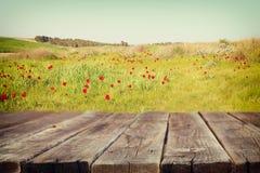 Tabla de madera del tablero delante del paisaje del verano del campo con muchas flores Se empaña el fondo imagenes de archivo
