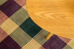 Tabla de madera en la estera multicolora fotos de archivo libres de regalías