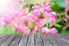 Tabla de madera en las flores de Antigonon Leptopus Imagen de archivo