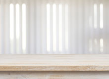 Tabla de madera en ventana defocuced con el fondo de la persiana imagenes de archivo