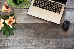 Tabla de madera femenina del escritorio de la oficina con el ordenador portátil y la flor Visión superior con el espacio de la co Imágenes de archivo libres de regalías