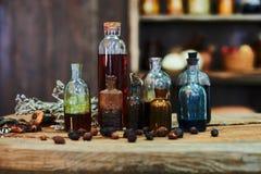 Tabla de madera, hierbas secadas, botellas, una visión superior, en el estudio, por la tarde Fotos de archivo libres de regalías