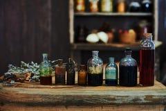Tabla de madera, hierbas secadas y botellas, una visión superior, en el estudio, por la tarde Foto de archivo