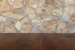 Tabla de madera marrón vieja con la pared de piedra borrosa del bloque en fondo ligero del sitio imagenes de archivo