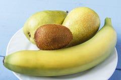 Tabla de madera rústica con la fruta de las peras, del plátano y de kiwi en la placa blanca Desayuno o cena sano con las comidas  Fotos de archivo
