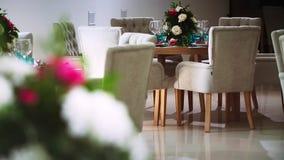 Tabla de madera redonda alrededor de la cual hay sillas y dentro del pasillo del banquete almacen de video