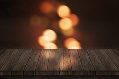 Tabla de madera vacía con las luces ámbar Empañado, luces del bokeh en fondo Foto de archivo libre de regalías