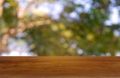 Tabla de madera vacía delante del verde borroso abstracto del fondo de la luz del jardín y de la naturaleza Para la exhibición o  foto de archivo