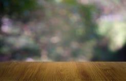 Tabla de madera vacía delante del verde borroso abstracto del fondo de la luz del jardín y de la naturaleza Para la exhibición o  imagenes de archivo