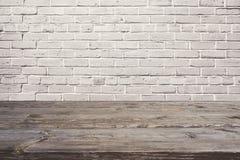 Tabla de madera vacía sobre la pared de ladrillo blanca Fondo para el montaje del producto imagen de archivo