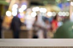 Tabla de madera vac?a de marr?n en fondo colorido borroso frente, para la presentaci?n y el producto y la plantilla de la publici fotografía de archivo libre de regalías