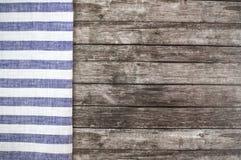 Tabla de madera vieja con un mantel rayado azul fotos de archivo libres de regalías
