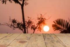 Tabla de madera y opinión de la puesta del sol sobre fondo Fotos de archivo
