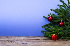 Tabla de madera y ramas spruce con las decoraciones de la Navidad en fondo coloreado brillante Imagen de archivo