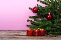 Tabla de madera y ramas spruce con las decoraciones de la Navidad en fondo coloreado brillante Fotografía de archivo libre de regalías