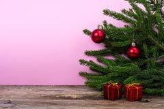 Tabla de madera y ramas spruce con las decoraciones de la Navidad en fondo coloreado brillante Imágenes de archivo libres de regalías