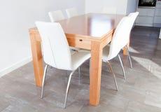 Tabla de madera y sillas blancas Imagenes de archivo