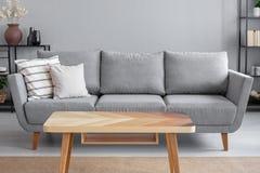 Tabla de madera y sofá gris grande con las almohadas en sala de estar del apartamento de moda, foto real fotografía de archivo libre de regalías
