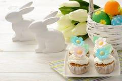 Tabla de Pascua - cesta con los huevos, los molletes y los conejitos en la tabla de madera Fotos de archivo