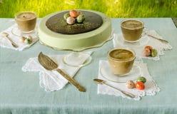 Tabla de Pascua con el pastel de queso del matcha del té y el café con leche en fondo de la hierba verde Imagen de archivo