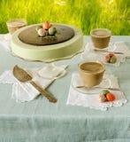 Tabla de Pascua con el pastel de queso del matcha del té y el café con leche en fondo de la hierba verde Imágenes de archivo libres de regalías