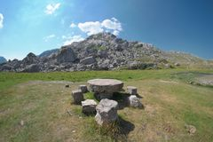 Tabla de piedra redonda y asientos de piedra foto de archivo