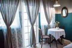 Tabla de té fijada con los potes de la planta al lado de ventanas grandes y de cortinas grises grandes con el filtro de la luz de fotos de archivo