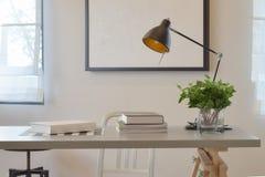 Tabla de trabajo con la lámpara del libro, y el florero en casa Imágenes de archivo libres de regalías
