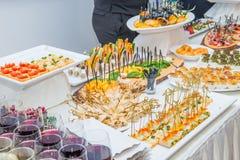Tabla del abastecimiento con los platos de la comida, los bocados y las bebidas alcohólicas y sin alcohol para las huéspedes del  Imagen de archivo libre de regalías