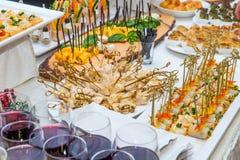 Tabla del abastecimiento con los platos de la comida, los bocados y las bebidas alcohólicas y sin alcohol para las huéspedes del  Fotos de archivo