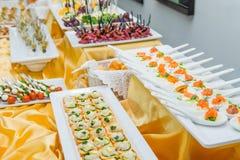 Tabla del abastecimiento con los platos y los bocados en el evento del negocio en el pasillo del hotel Servicio en la reunión de  Fotos de archivo