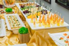 Tabla del abastecimiento con los platos y los bocados en el evento del negocio en el pasillo del hotel Servicio en la reunión de  Fotografía de archivo