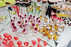 Tabla del abastecimiento de la boda con los diversos dulces y tortas Fotografía de archivo libre de regalías