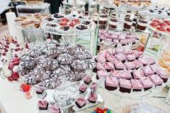 Tabla del abastecimiento de la boda con los diversos dulces y tortas Fotografía de archivo