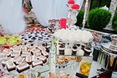 Tabla del abastecimiento de la boda con los diversos dulces y tortas Foto de archivo