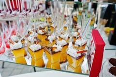 Tabla del abastecimiento de la boda con los diversos dulces y tortas Fotos de archivo libres de regalías
