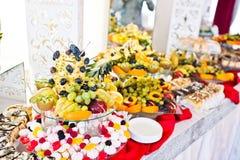 Tabla del abastecimiento de la recepción nupcial con las diversas frutas y tortas Fotografía de archivo libre de regalías