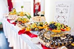 Tabla del abastecimiento de la recepción nupcial con las diversas frutas y tortas Fotos de archivo libres de regalías