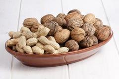 Tabla del blanco del cuenco del manojo de los cacahuetes de las nueces Fotografía de archivo