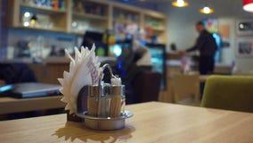Tabla del café con primero plano de las servilletas y camarero borroso en el trabajo Fotografía de archivo