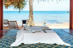 Tabla del café en una playa arenosa tropical con el mar en el fondo, isla del conejo, Camboya Imágenes de archivo libres de regalías