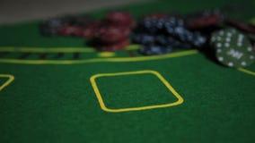 Tabla del casino con las manos y el naipe del jugador de póker metrajes