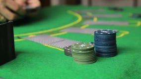 Tabla del casino con las manos y el naipe del jugador de póker almacen de metraje de vídeo