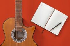 Tabla del escritor de la canción un espacio de trabajo con la guitarra acústica del músico y el papel de la libreta imagen de archivo libre de regalías
