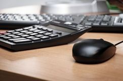 Tabla del escritorio con el teclado, la calculadora y el ratón Foto de archivo libre de regalías