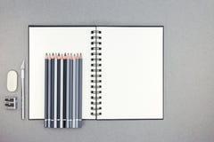 Tabla del escritorio de oficina con el cuaderno espiral abierto, lápices, borrador, kn Fotografía de archivo libre de regalías