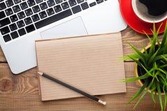 Tabla del escritorio de oficina con el ordenador, las fuentes, la taza de café y la flor