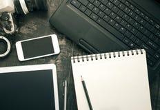 Tabla del escritorio de oficina con el ordenador, las fuentes y la tableta, pho móvil foto de archivo libre de regalías