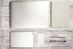 Tabla del escritorio de oficina con el ordenador portátil, la libreta, la pluma y otra fuentes Fotografía de archivo libre de regalías